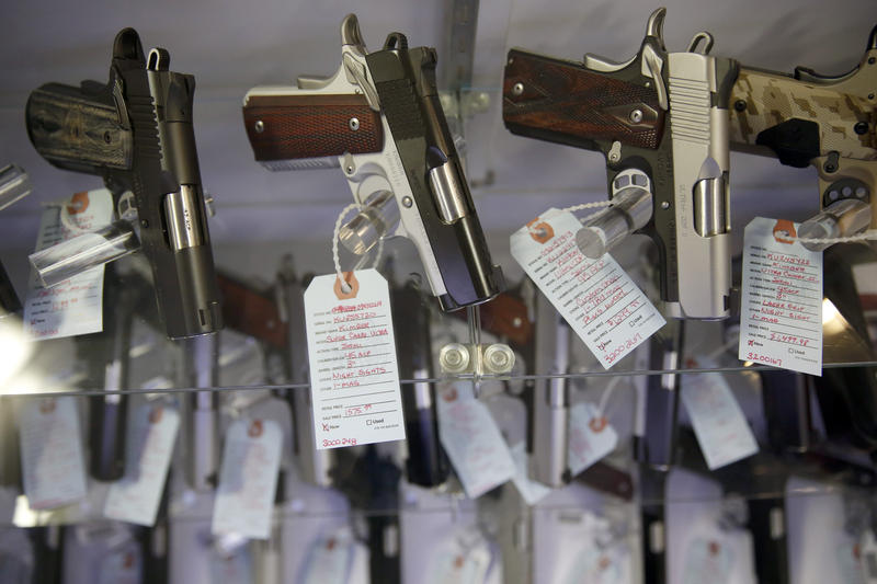 In this Saturday, Nov. 15, 2014 photo, handguns sit in a glass display case at Metro Shooting Supplies, in Bridgeton, Mo.