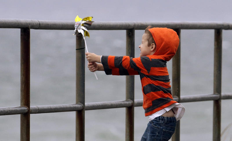 In this file photo from Nov 17th 2015, Jacob Bell, 4, holds a pinwheel toy into a high wind, with heavy surf behind him on a pier in Seattle.