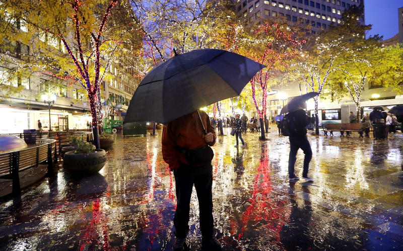 Pedestrians protect themselves from a steady evening rain as they walk or pause near colorful holiday lights Monday, Nov. 18, 2013, in downtown Seattle.
