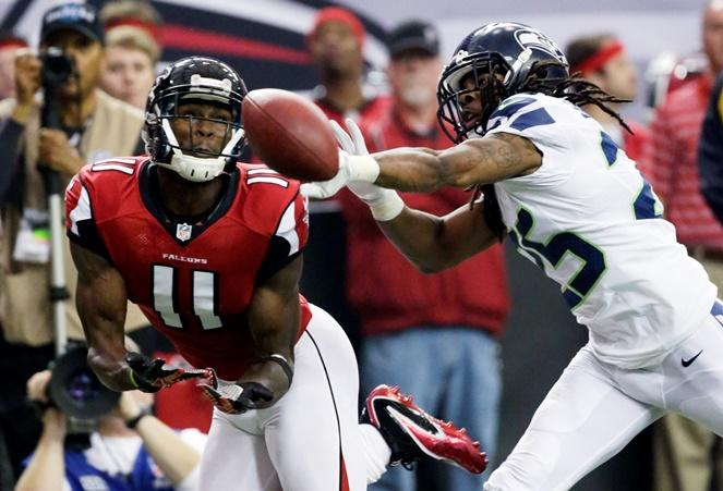 Atlanta Falcons wide receiver Julio Jones (11) misses a catch as Seahawks cornerback Richard Sherman (25) defends during the NFC divisional playoff NFL football game Jan. 13, 2013, in Atlanta.