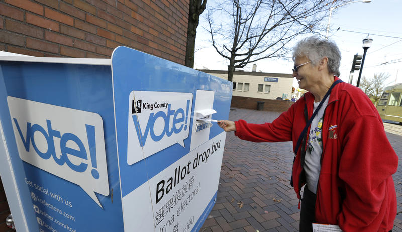 Barb Kearney-Schupp deposits her vote-by-mail ballot in a collection box, Thursday, Nov. 3, 2016, at Seattle Central College in Seattle.