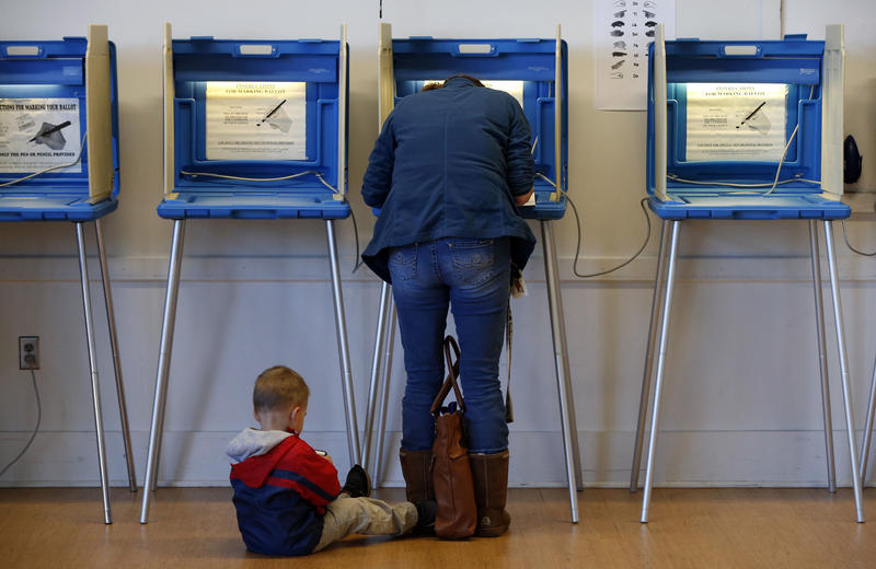A boy takes a seat as his mother votes at Precinct 11 at City Hall Tuesday, Nov. 8, 2016, in Bloomington, Minn.