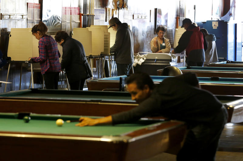 Residents of Chicago' 33rd Ward, background, mark their ballots as others shoot pool at Marie's Golden Cue pool hall Tuesday, Nov. 8, 2016.