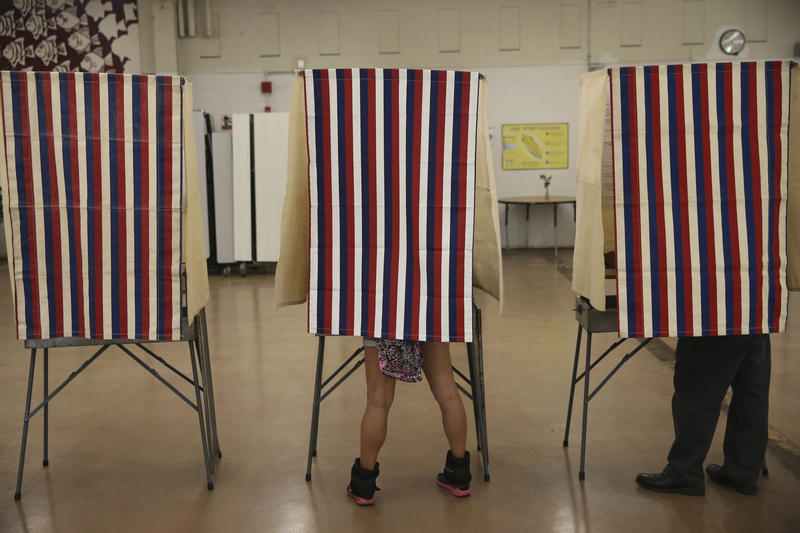 Voters cast their ballots in booths at Farrington High School, Tuesday, Nov. 8, 2016, in Honolulu.
