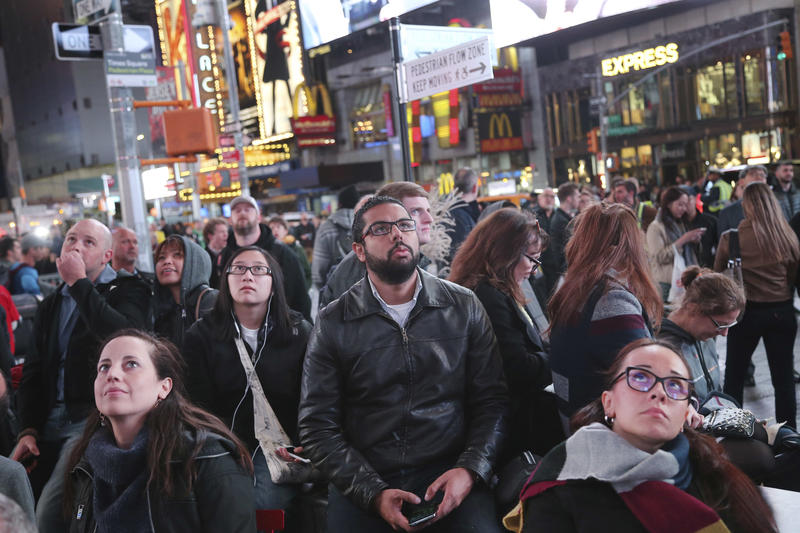Pedestrians watch the election results on large screens in Times Square, New York, Tuesday, Nov. 8, 2016.