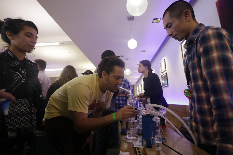 Seibo Shen, at right, provides marijuana to smoke for supporters of Prop 64 during a rally at Sparc Dispensary Tuesday, Nov. 8, 2016, in San Francisco.