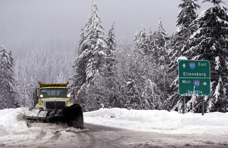 In this Dec. 22, 2015, file photo, a snowplow clears an overpass of freshly fallen snow over Interstate 90 at Snoqualmie Pass, Wash.