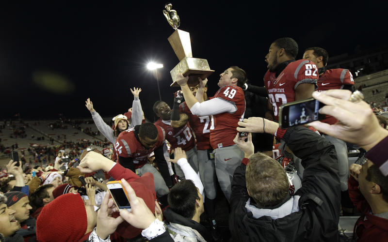 Washington State kicker Andrew Furney (49) holds the Apple Cup Trophy as he celebrates with teammates after they defeated Washington 31-28 in overtime on Friday, Nov. 23, 2012, in Pullman, Wash. Furney kicked the game-winning field goal.