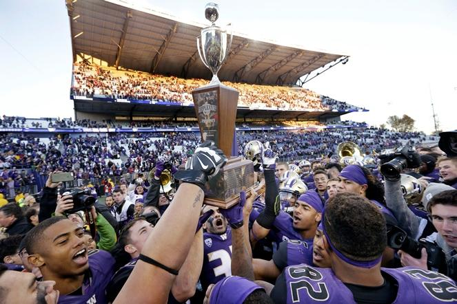 Washington players heft the Apple Cup trophy after beating Washington State in the annual football rivalry Friday, Nov. 27, 2015, in Seattle. Washington won the annual Apple Cup, 45-10.