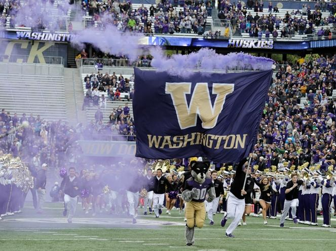 A Washington flag with purple smoke and the team mascot Harry the Husky leads the team on the field at a game against Portland State, Saturday, Sept. 17, 2016, in Seattle.