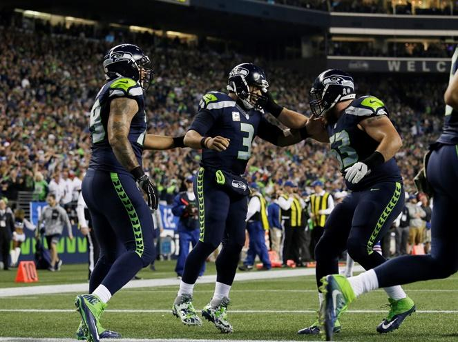 Seahawks quarterback Russell Wilson, center, celebrates his touchdown with tackle Garry Gilliam, left, and offensive guard Mark Glowinski, right, in the first half of a game against the Buffalo Bills, Monday, Nov. 7, 2016, in Seattle.