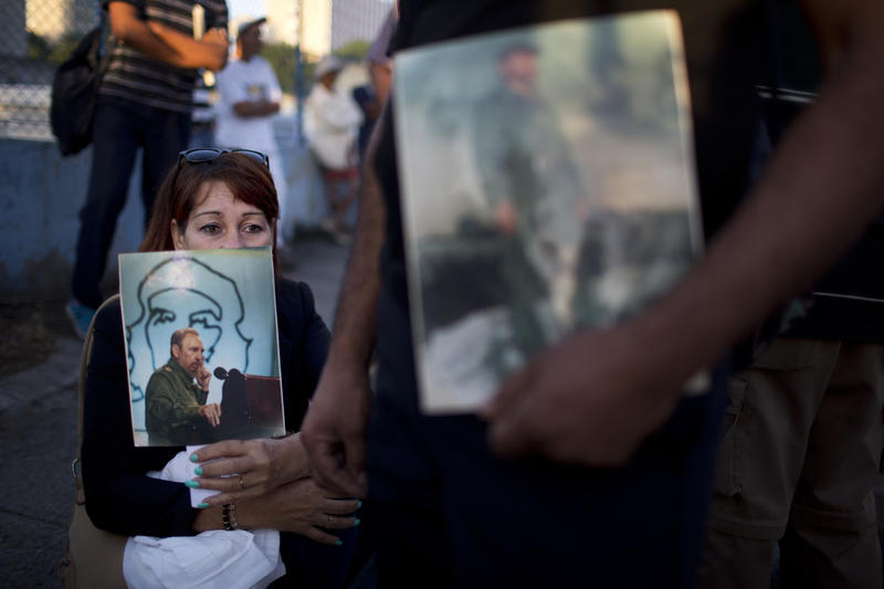 A woman holds an image of the late Fidel Castro as she waits in line to pay her final respects to the late leader, in Havana this week.