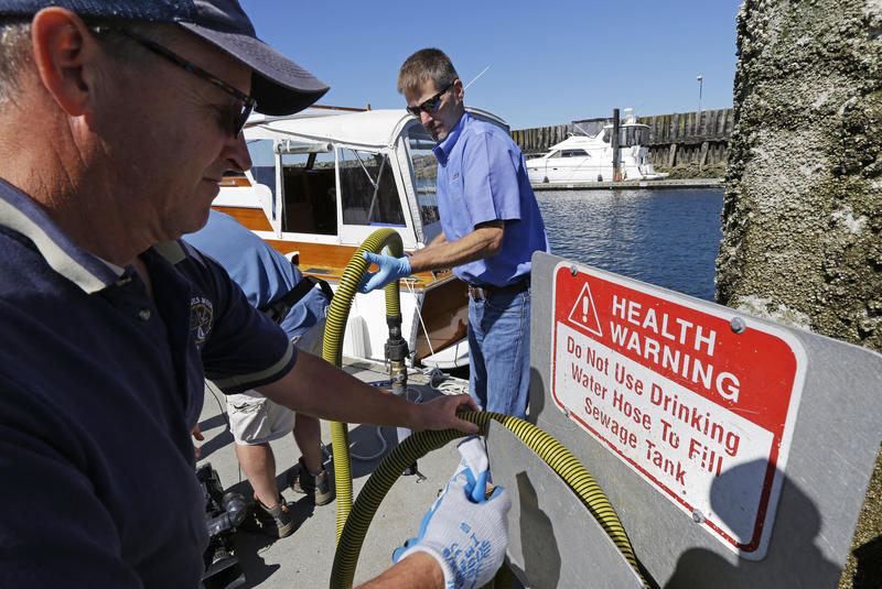 Todd Powell (right), of Federal Way, Wash., helps Pat Wolfrom, (left) put away the hose from a sewage pump-out station, as the state announced its petition to EPA this summer for a ban on all dumping of sewage in Puget Sound.