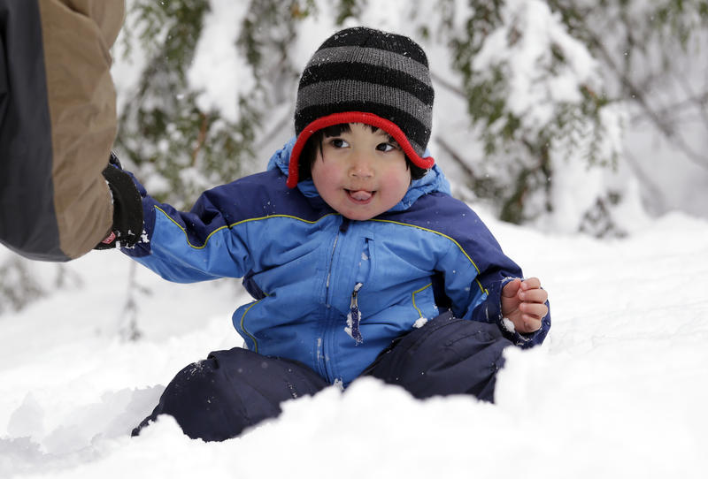 Leon Perkins, 3, sits in a snowbank as his father helps him put on mittens Tuesday, Dec. 22, 2015, at Snoqualmie Pass, Wash. The Seattle family headed to the mountains to enjoy the snow, which also may be necessary this weekend.