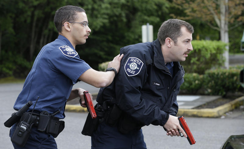 In this photo taken May 6, 2015, Seattle police recruits Tre Smith, left, and Travis Duennes work together through a practice scenario at the Washington State Criminal Justice Training Commission in Burien, Wash.