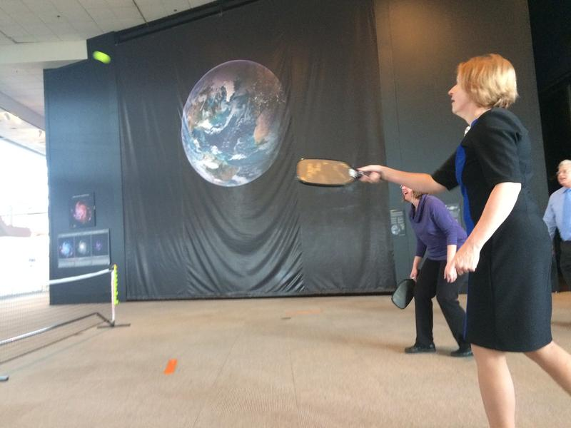 A representative from the Washington State Department of Commerce demonstrates a pickleball paddle made from plane scraps at the Museum of Flight in Seattle.