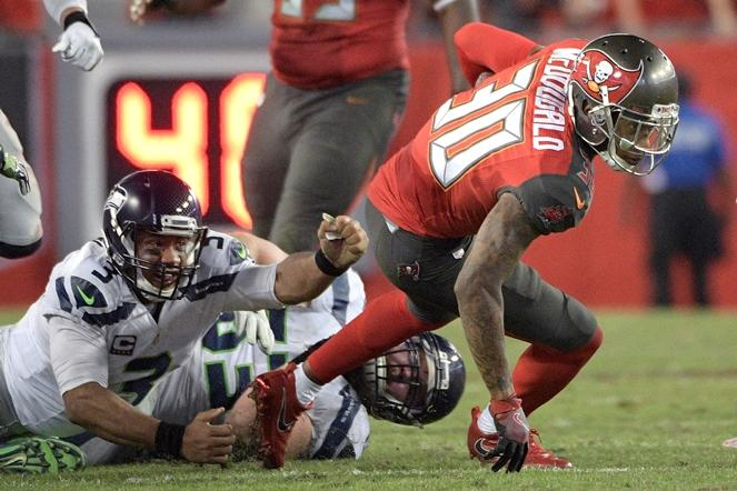 Buccaneers free safety Bradley McDougald (30) slips an arm tackle by Seahawks quarterback Russell Wilson (3) and center Joey Hunt (53) after intercepting a pass by Wilson on Sunday, Nov. 27, 2016. The Buccaneers won 14-5.