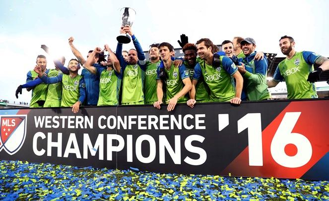 Seattle Sounders players celebrate with the trophy after defeating Colorado in the second leg of the MLS Western Conference soccer finals Sunday, Nov. 27, 2016, in Commerce City, Colo.