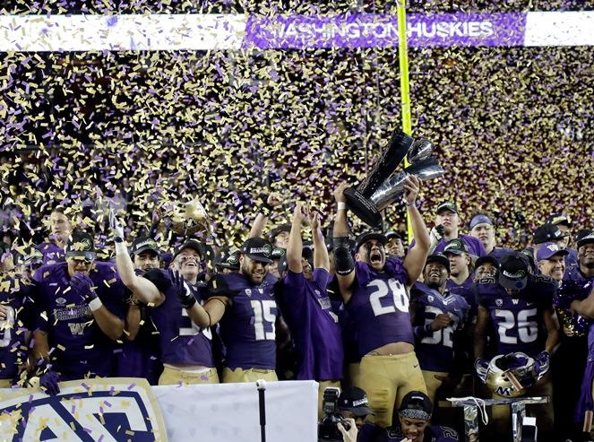 Washington players celebrate with the trophy after a 41-10 win over Colorado in the Pac-12 Conference championship NCAA college football game Friday, Dec. 2, 2016, in Santa Clara, Calif.