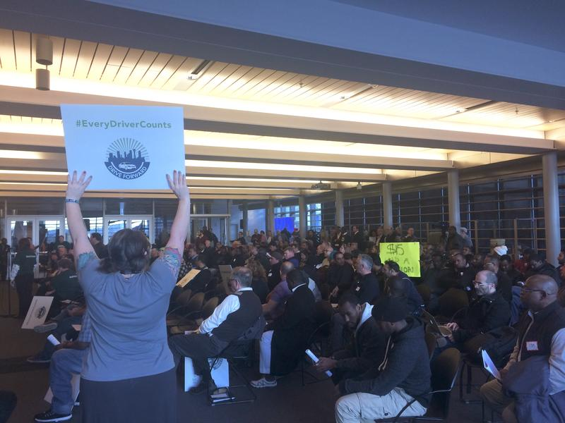 "One woman holds up an ""Every Driver Counts"" sign while another holds one that says ""$15 and a Union"" at a packed meeting about for-hire driver unionization at Seattle City Hall."