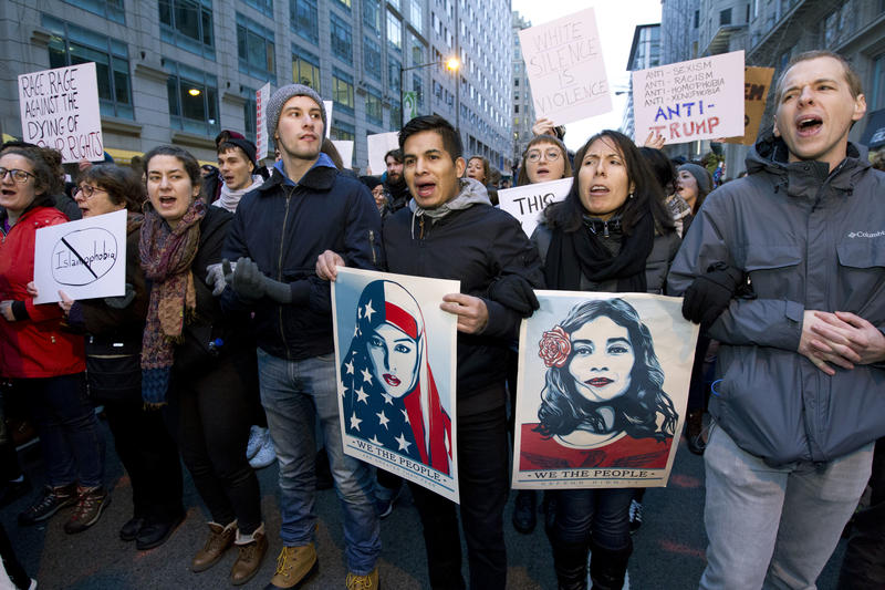 Demonstrators march on the street near a security checkpoint inaugural entrance, Friday, Jan. 20, 2017 in Washington, ahead of President-elect Donald Trump's inauguration.