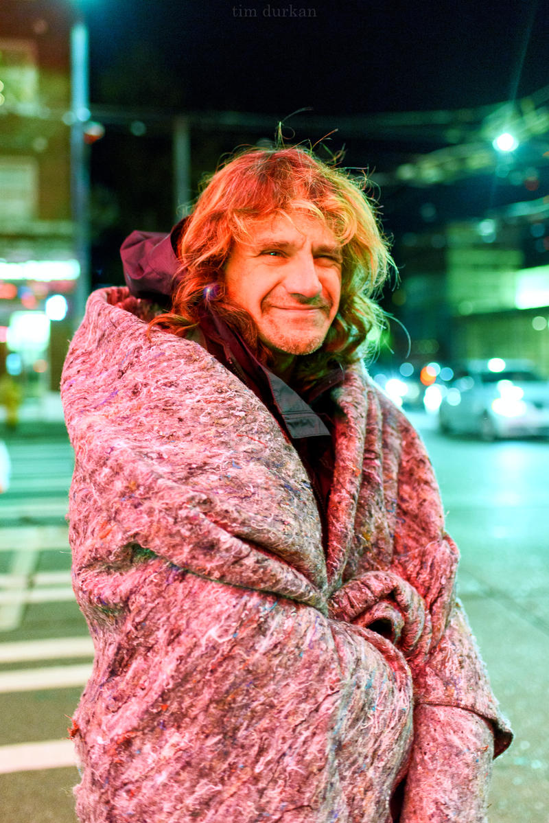 A man named Rodger tries to stay warm on a cold winter's night in Seattle.