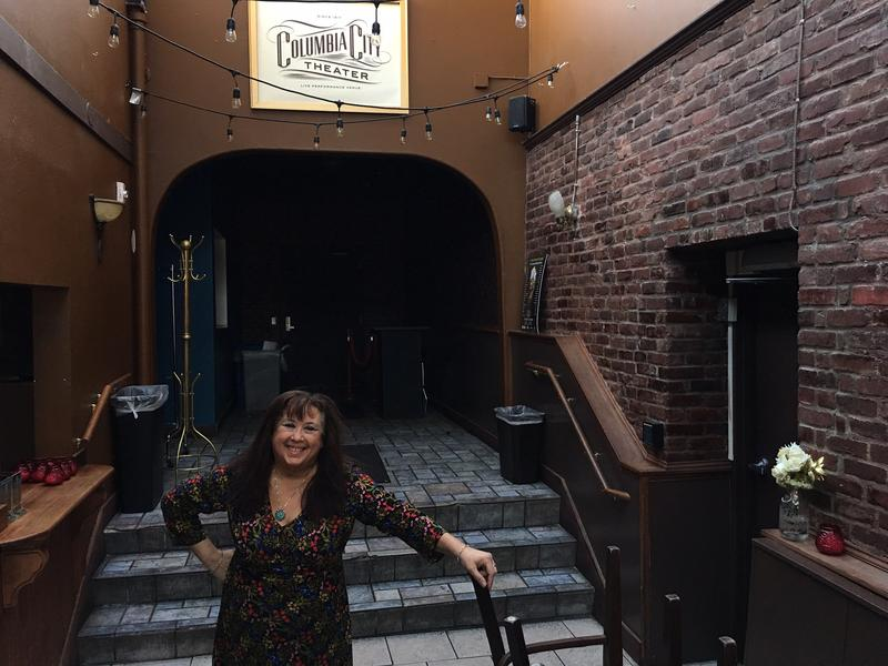 Lara Lavi stands in the atrium of the Columbia City Theater, celebrating its centennial in 2017. She's co-owned and managed this space for about a year.