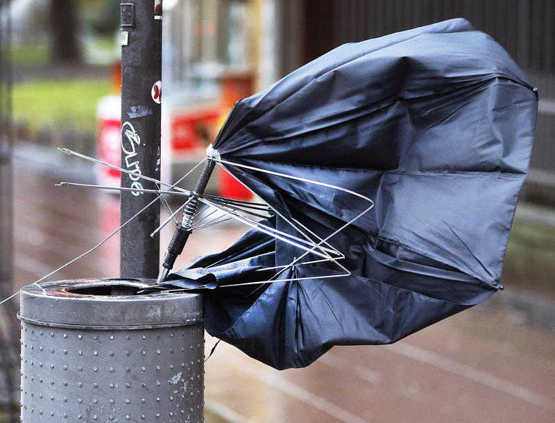 A wrecked umbrella was thrown into a trash can during heavy winds and rain.