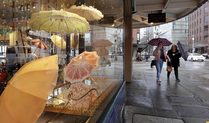 Pedestrians under umbrellas pass a vintage umbrella shop Wednesday, Jan. 18, 2017, in downtown Seattle.