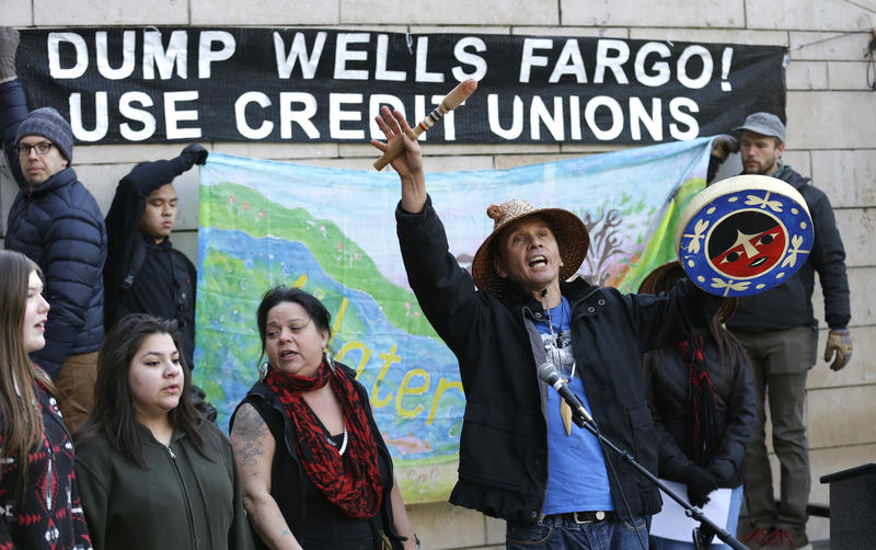 Paul Wagner, center, of the Saanich Nation on Vancouver Island, bangs a drum and sings as he takes part in a protest against the Dakota Access Pipeline and the City of Seattle's use of Wells Fargo Bank.