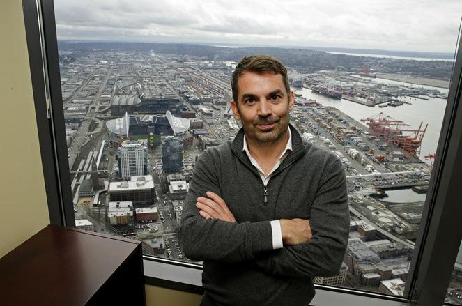 Chris Hansen, the investor hoping to build an arena to house a possible NBA or NHL franchise in Seattle's SoDo district, poses for a photo in front of a window showing CenturyLink Field and Safeco Field, on Thursday, Feb. 16, 2017.