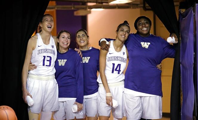Washington starters Katie Collier (13), Natalie Romeo, Kelsey Plum, Heather Corral (14) and Chantel Osahor pull a curtain aside as they look into the arena before player introductions against Washington State  on Dec. 27, 2016, in Seattle.
