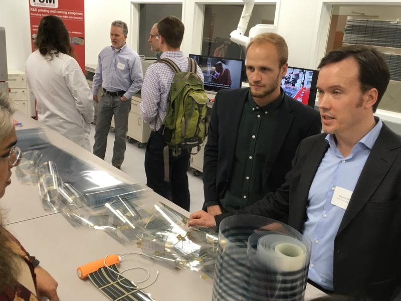 Martin Kiener (right) the CEO of FOM Technologies, with examples of the photovoltaic cells that the company prints on plastic sheeting to manufacture solar panels at a fraction of the cost of silicon or glass.