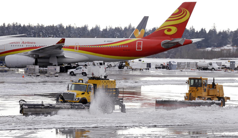 Snowplows clear wet snow at Sea-Tac Airport on Monday. Flights were canceled or delayed as a result of the unusual accumulation of snow.