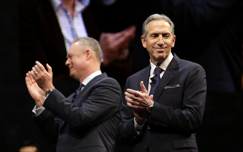 Outgoing Starbucks CEO Howard Schultz (right) and his successor Kevin Johnson applaud at the company's annual shareholders meeting at McCaw Hall in Seattle.