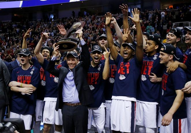 Gonzaga head coach Mark Few holds a trophy with his team after beating Xavier during an NCAA Tournament college basketball regional final game Saturday, March 25, 2017, in San Jose, Calif.