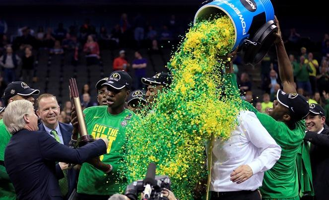 Oregon players celebrate with coach Dana Altman after the Midwest Regional final against Kansas in the NCAA men's college basketball tournament, Saturday, March 25, 2017, in Kansas City, Mo. Oregon won 74-60.