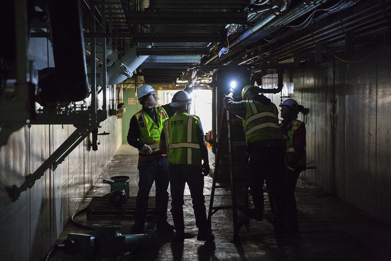 Workers at the West Point Treatment plant hanging lights along the tunnels that were damanged during the flooding.