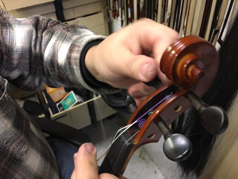 Luthier Rick Wickland restrings a violin, at Hammond Ashley Violins in Issaquah.