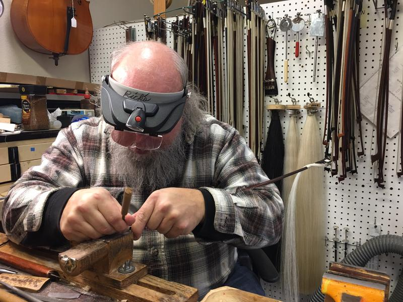 Veteran luthier Rick Wickland works on part of a violin bow at his work bench inside Hammond Ashley Violins, in Issaquah. The horse hair used on the bow is hanging behind him.
