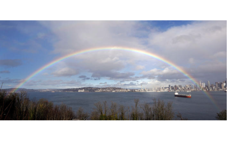 A rainbow arc fills the sky and spreads across Elliott Bay and downtown Seattle between rain showers Thursday, Feb. 9, 2017.