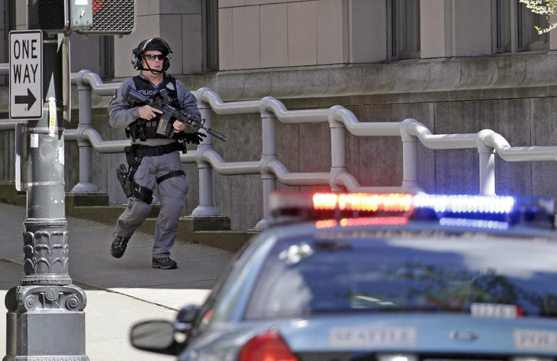 A police officer carrying a rifle runs past a downtown building and near the scene of a shooting involving several police officers in downtown Seattle, Thursday, April 20, 2017.