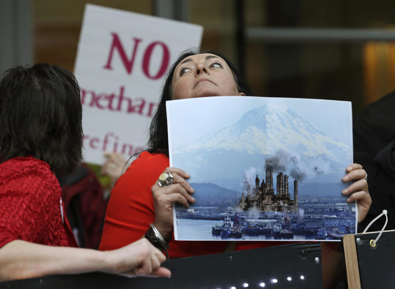 In this photo taken Feb. 10, 2016, Francesca Siena holds a photo of Mount Rainier and the Port of Tacoma that has been computer modified to include the image of a refinery as she protests in Tacoma, Wash. Many simlar concerns relate to permitting for LNG.