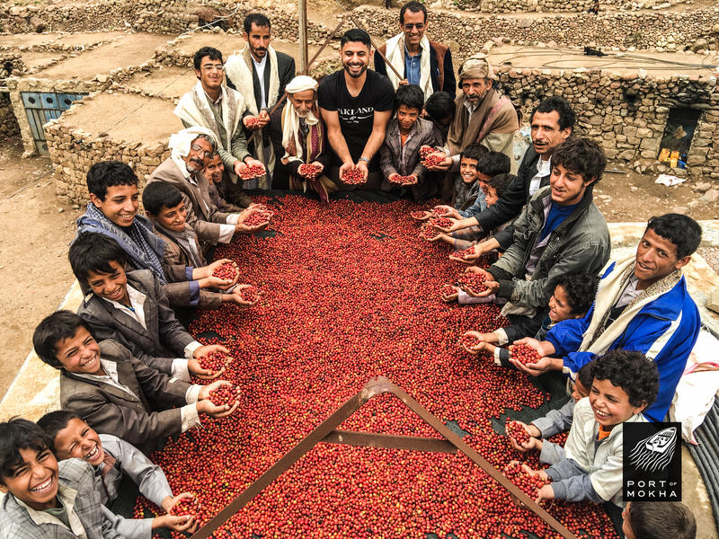 Mokhtar Alkhanshali with Yemeni coffee farmers and their red coffee berries.