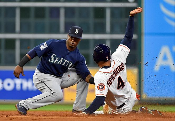 Houston Astros' George Springer is tagged out by Mariners shortstop Jean Segura while attempting to steal second during the third inning of a game, Tuesday, April 4, 2017, in Houston.