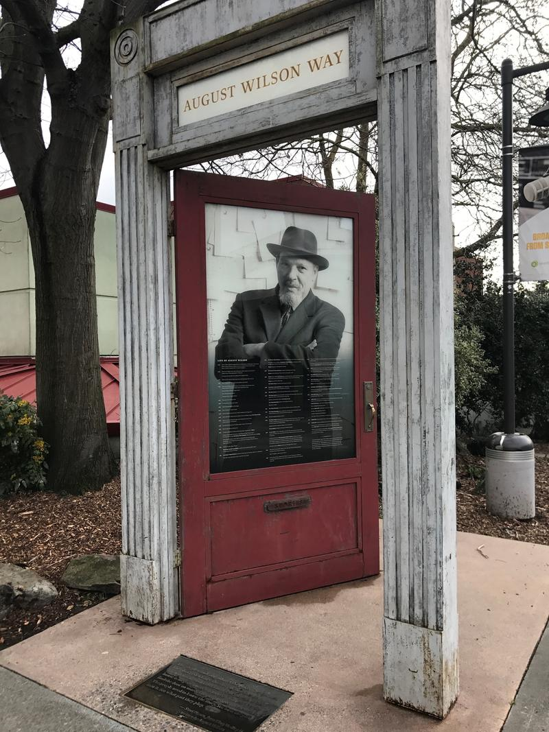 A free standing stone doorframe with a red door and a photo of August Wilson pays tribute to the playwright at Seattle Center