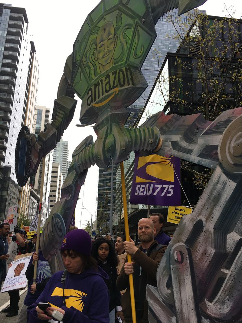 Demonstrators at May Day in Seattle hold up a robot with Amazon CEO Jeff Bezos' likeness in front of the company's downtown headquarters.
