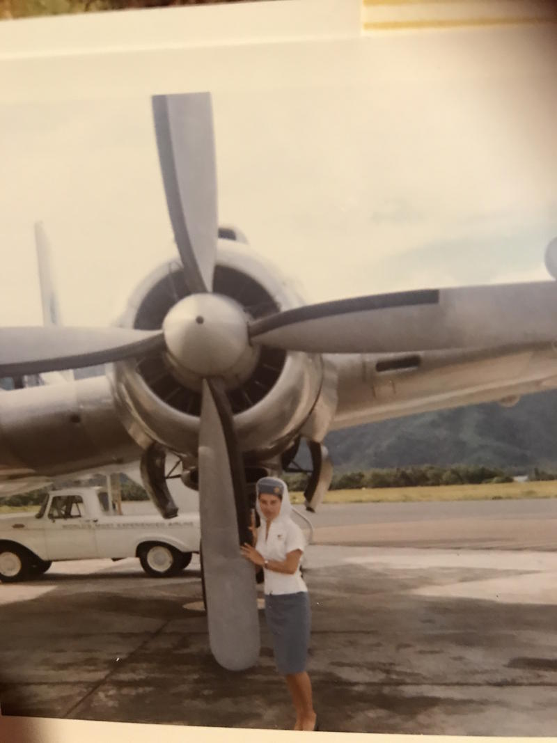 Gloria Sferra standing outside a Pan American prop plane in Fiji.