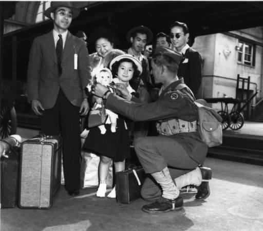 Yukie Suekawa, 6, and Private Howard L. Loudermilk at Tacoma's Union Station as the city's Japanese-American residents were sent off to a California internment camp