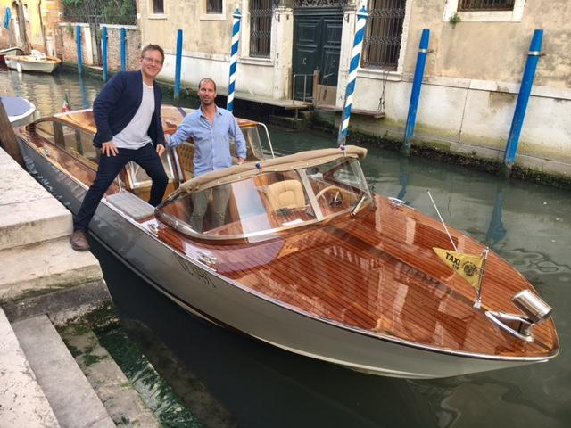 KNKX travel expert Matthew Brumley steps onto a private water taxi in Venice.